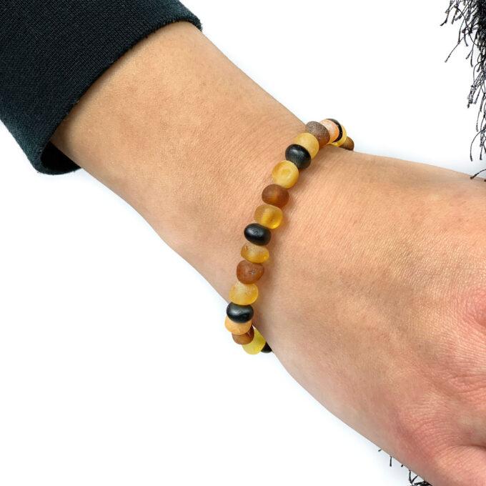 unpolished multi color amber bracelet on hand