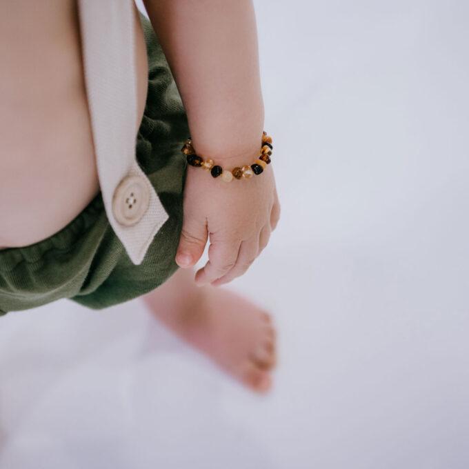 baby wearing colourful amber teething bracelet