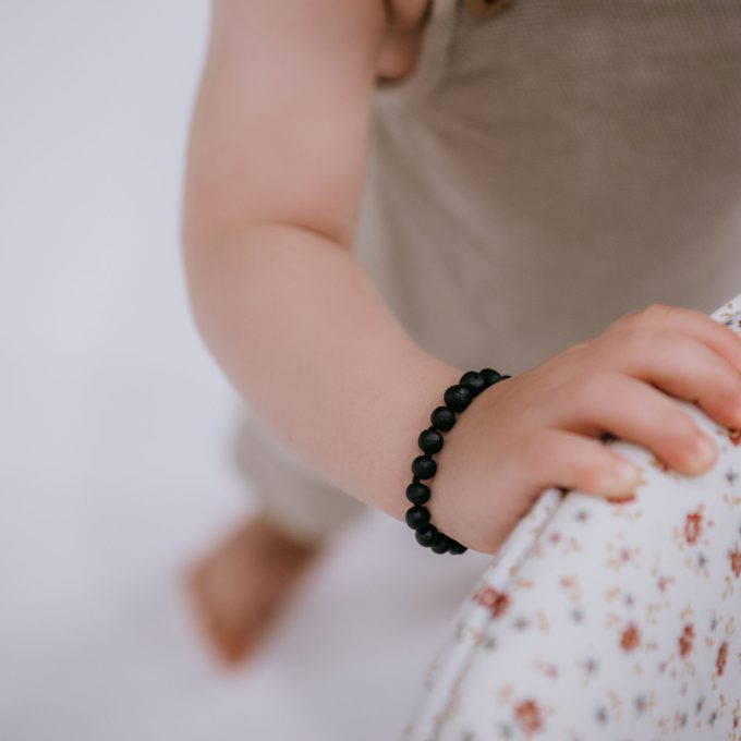 raw black amber teething bracelet on baby arm
